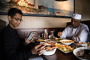 Ahmed Mohamed takes a photo of his crab legs at dinner with his father and younger brother at Red Lobster in Irving, Texas on July 15, 2016. (Cooper Neill for The Washington Post)