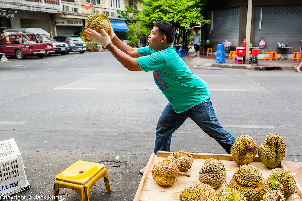 27 APRIL 2013 - BANGKOK, THAILAND:   A man sets up a street stand to sell durian, a fruit popular in Thailand, along Chareon Krung Road, a main street in Talat Noi. The Talat Noi neighborhood in Bangkok started as a blacksmith's quarter. As cars and buses replaced horse and buggy, the blacksmiths became mechanics and now the area is lined with car mechanics' shops. It is one the last neighborhoods in Bangkok that still has some original shophouses and pre World War II architecture. It is also home to a  Teo Chew Chinese emigrant community.         PHOTO BY JACK KURTZ