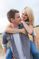 Romantic young man piggybacking woman on field