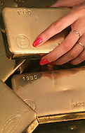 Gold ingots with woman's hand.<br /> <br /> Larger JPEG + TIFF images available by contacting use through our contact page at : www.effectiveworkingimage.com