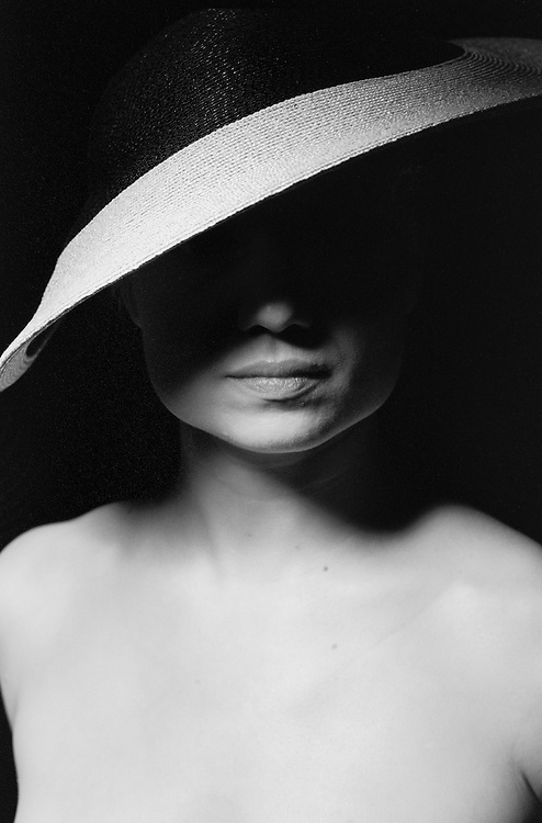 Portrait of woman in hat, eyes obscured.