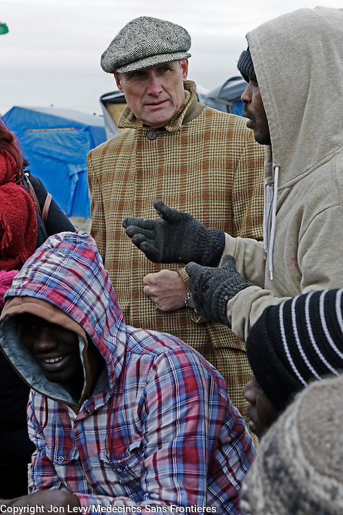 Writer AA Gill talks with refugees from Darfur, Sudan, in the refugee camp in Calais France. <br />
