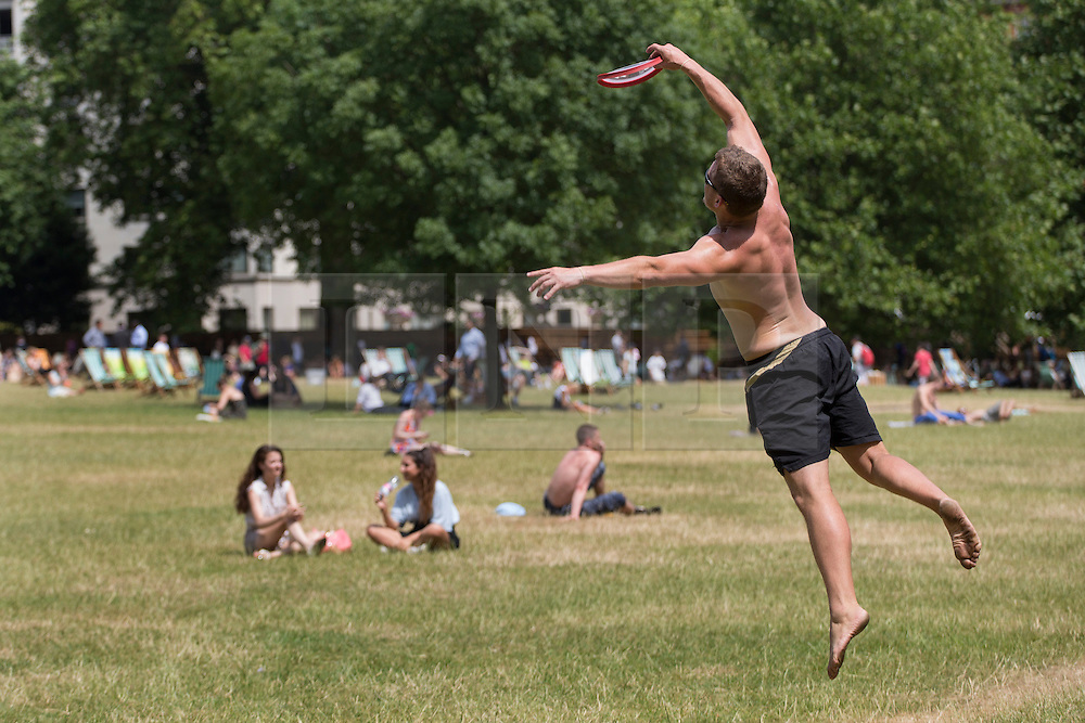 © licensed to London News Pictures. London, UK 16/07/2013. People playing frisbee as they enjoy the sunshine and hot weather in Green Park, London on Tuesday, 16 July 2013. Photo credit: Tolga Akmen/LNP