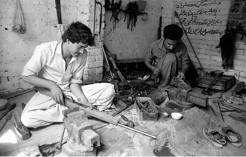 Pakistan 1986 .Darra Adamkhel is Pakistan's largest weapons bazaar and factory, renowned for its gun making expertise since the late 19th century, Darra is a sprawl of hundreds of workshops where some 3,500 gunsmiths toil on replica weapons..Workshop where the rifles are built