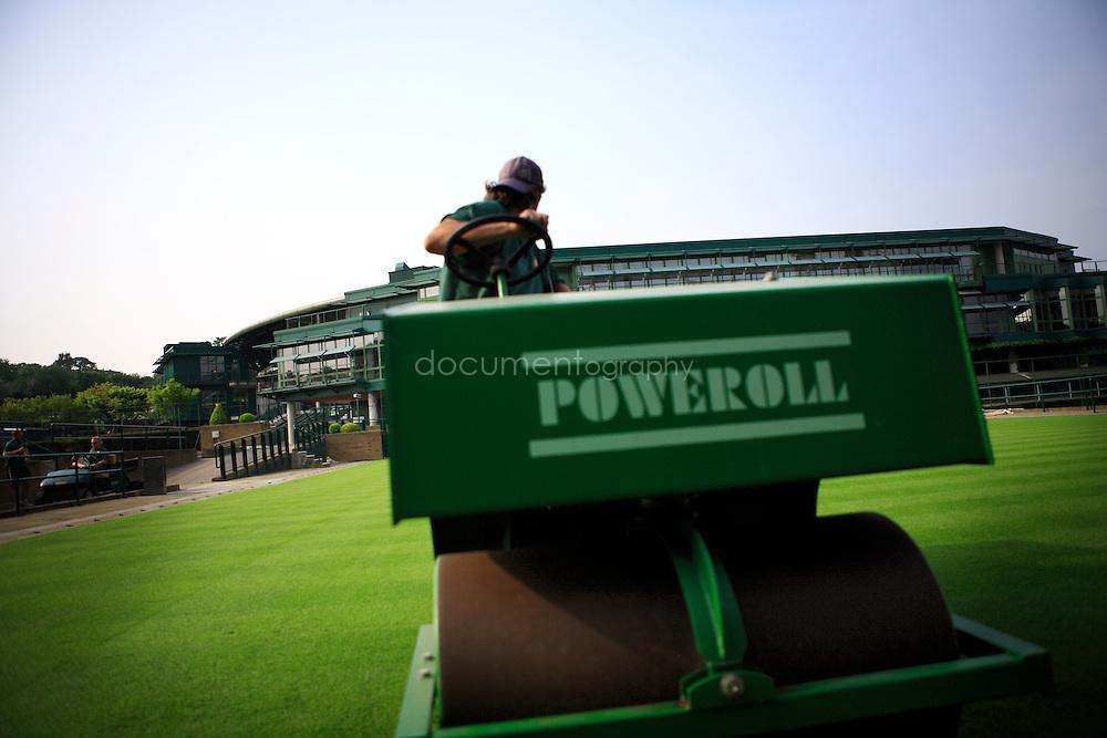 A gardener compacts the grass of one of Wimbledon's tennis court