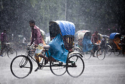 July 23, 2017 - Dhaka, Dhaka, Bangladesh - Rickshaw puller carrying passenger when heavy rainfall maid in the Dhaka, Bangladesh on July 23, 2017. (Credit Image: © Km Asad/NurPhoto via ZUMA Press)