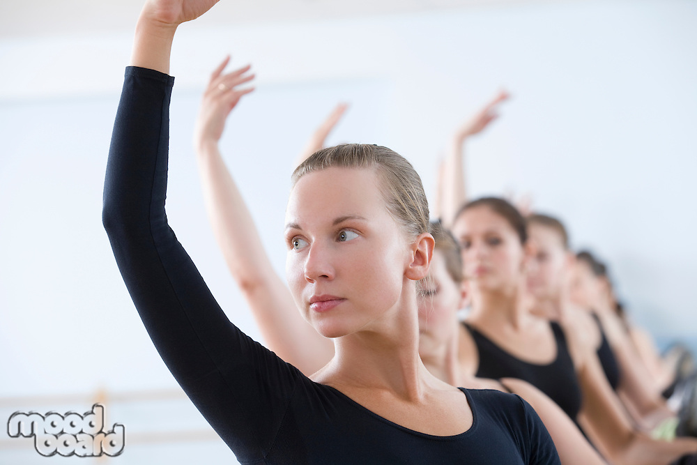 Young women with arms raised at the barre