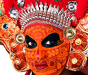 A ROAD-SWEEPER YESTERDAY, A GOD TODAY<br /> <br /> A 19th century Indian missionary once said: There are certain places that are rarely seen; and in those you will find a special sort of magic<br /> <br /> Theyyam is one of those magical celebrations that takes place annually in South India.<br /> <br /> It's a religious dance-drama that takes place in just two districts of Kerala; in Kannur and Kasargod, and is celebrated during the months of December - February. Believed to pre-date Hinduism, Theyyam is said to be a corrupted form of the word Deivam meaning God and Aattam meaning Dance. The meaning of Theyyam thus becomes Dance of the Gods.  <br /> <br /> It's a ritual art form at least 1,500 years old combining both religious and spiritual traditions; and Theyyam appear in more than 450 forms.<br /> <br /> The male participants all come from the Dalit caste - that is the lowest caste in India, previously referred to as Untouchables. <br /> Dalits have traditionally taken on the most anti-social and menial jobs, such as road-sweeping, cleaning sewers and refuse-collection.<br /> Yet during the Theyyam season they give up these jobs and metamorphose into an incarnation of a God. They will not eat meat or fish, and are forbidden to sleep with their wives. <br /> <br /> The right to perform as a Theyyam is inherited and passed down solely through the mother's family; and only men may become a Theyyam. <br /> It is not a profession or calling that can be adopted, and the transition from Dalit to Deity - becoming the Incarnation of the God -  is only achieved after intense physical and spiritual preparation.<br /> <br /> Before entering a village shrine, Theyyam artistes will lie on the floor of a nearby shed for for up to five hours beforehand while their acolytes paint the most intricate designs on their face, each element of which has a particular symbolism. <br /> After donning the elaborate costume, their head-dress is finally put on, at which point for the first time, the Theyyam sees the reflection of himself in a hand-mirror.  <br /> An all-male orchestra of drummers