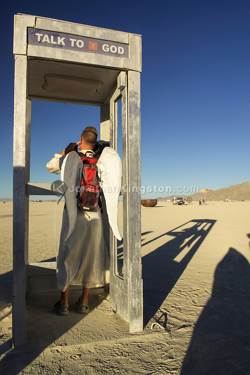 "BLACK ROCK CITY, NV:  A participant of Burning Man festival enjoys a lively conversation in a interactive art installment titled ""Talk To God"" by Brad Templeton in Black Rock City, Nevada."