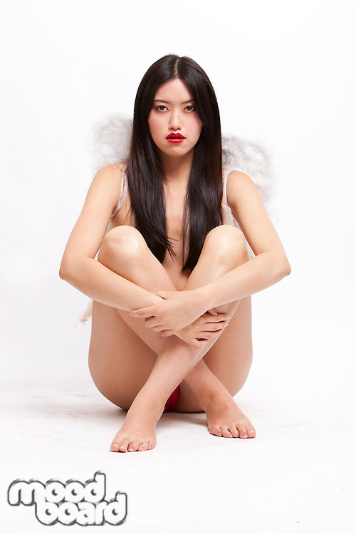 Portrait of young woman with angel wings sitting on floor against white background