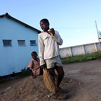 050709_Lusaka, Zambia Melanie Maxwell <br /> Two young boys take a break from sweeping dirt into a pile as they clean up the front yard of their home at a home for special needs boys inside a compound in Lusaka, Zambia on Thursday, May, 7 2009.