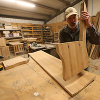 Keith puts the riser supports in place before fitting the bench and back in place for a new bench using old church pews.
