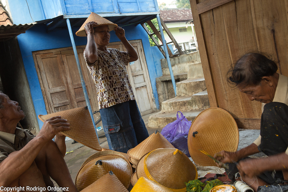 Marto, 70 (right), and Sukiyo, 66 (left), sell conical hats to a customer at their market stand in Mulo, Wonosari subdistrict, Gunung Kidul district, Yogyakarta Special Region, Indonesia.