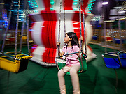 "12 DECEMBER 2018 - SINGAPORE:  A girl on a swing in a Christmas fair on Orchard Road. Orchard Road is the main shopping district of Singapore and for years hosts a large light display around Christmas. The main sponsor of this year's display is the Disney Company and the displays are decorated with characters from the Disney entertainment universe. This has upset some religious leaders in Singapore and the National Council of Churches of Singapore (NCCS) sent a letter to the Singapore Tourism Board (STB) expressing its concern about the ""increasing secularisation and commercialization of Christmas"" in Singapore. The STB reached out to the NCCS, but the Orchard Road lights will remain on through the holidays.   PHOTO BY JACK KURTZ"