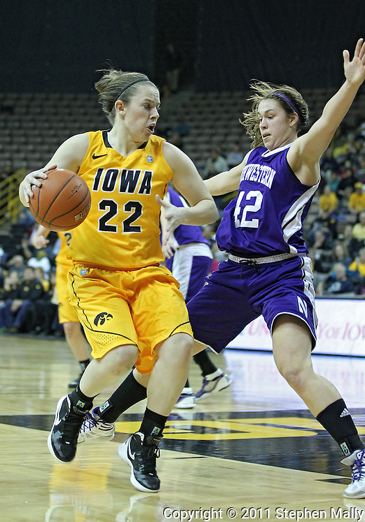 December 30, 2011: Iowa Hawkeyes guard Samantha Logic (22) drives against Northwestern Wildcats guard Karly Roser (42) during the NCAA women's basketball game between the Northwestern Wildcats and the Iowa Hawkeyes at Carver-Hawkeye Arena in Iowa City, Iowa on Wednesday, December 30, 2011.