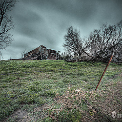 An old collapsing barn next to a road in south of Stafford, Kansas. The setting was a cloudy sunrise at the start of summer.