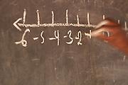 Teacher writing on a blackboard.