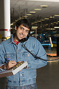 Cheerful man using telephone in factory