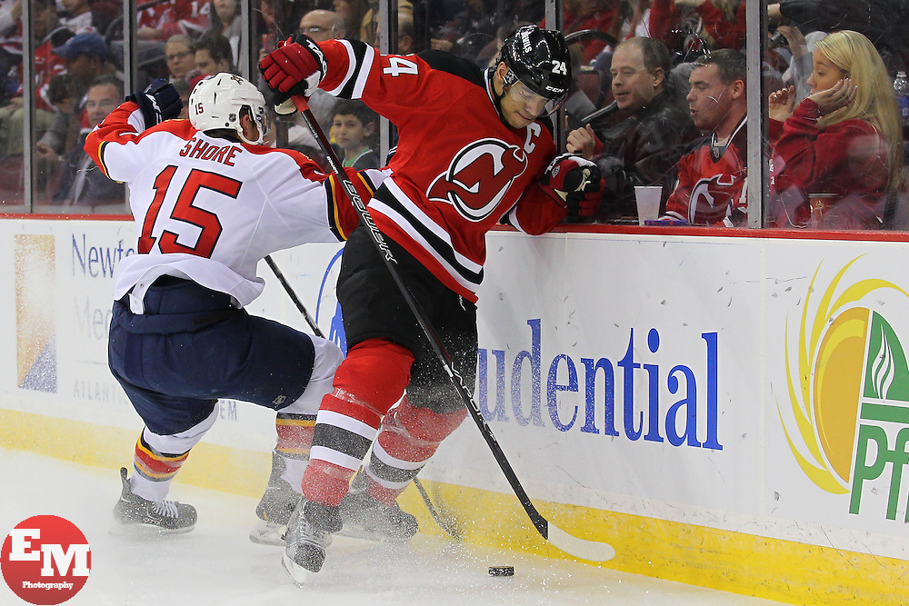 Mar 23, 2013; Newark, NJ, USA; New Jersey Devils defenseman Bryce Salvador (24) plays the puck away from Florida Panthers center Drew Shore (15) during the second period at the Prudential Center.
