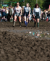 © Licensed to London News Pictures. 28/08/2015. Reading Festival, UK. Festival goers at Reading Festival walk through muddy conditions in wellington boots on Day 1 of the festivalPhoto credit: Richard Isaac/LNP