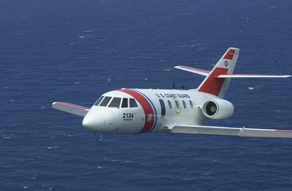 Aerial view of a United States Coast Guard HU-25 Falcon Jet, a medium-range surveillance fixed-wing aircraft., as seen from a USCG HH-65B helicopter, both stationed at Coast Guard Air Station Borinquen in Puerto Rico. The primary mission of the Station is search and rescue. The surrounding area around the airport was Ramey Air Force Base.  (U.S. Air Force photo/Master Sgt. Lance Cheung)