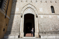 SIENA, ITALY - 20 MARCH 2015: A man steps outside the headquarters of the Monte dei Paschi di Siena bank at Palazzo Salimbeni in Siena, Italy, on March 20th 2015. <br /> <br /> Siena, a Tuscan city and UNESCO World Heritage Site, is home to Monte dei Paschi di Siena, the world's oldest surviving bank and Italy's third largest bank. The bank, founded in 1472, was the largest employer in Siena, and it helped finance a host of community projects and services until it stumbled during the financial crisis started in 2008.