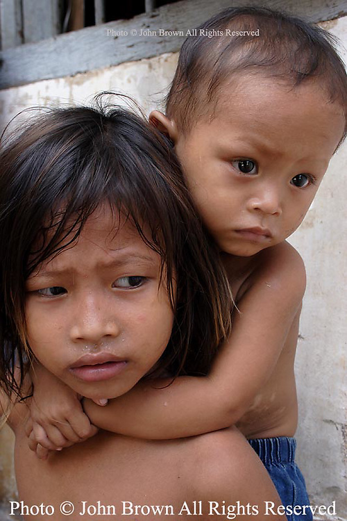 A young Khmer girl carries a young boy at a temple near a squatter's village in Phnom Penh, Cambodia. The children are residents of an adjacent squatter's slum that is located less than one block from Phnom Penh's main tourist strip.  The pair is among the nearly five-million Cambodians (about 35%) that The World Bank estimates exist on roughly 2000 riels ($.50 USD) per day.