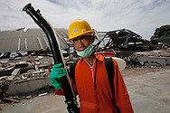 Padang, Western Sumatra, Indonesia, 7th October 2009:?19 year old Rafio Perdana Ali prepares to spray disinfectant on the remains of the  Padang STDB Prayoga English school where 20 students died following a devastating earthquake in Western Sumatra that claimed the lives of an estimated 2000 people.?Photo: Joseph Feil