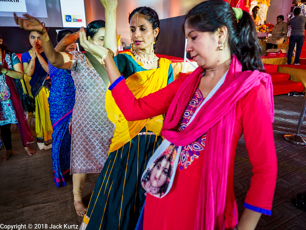 """23 SEPTEMBER 2018 - BANGKOK, THAILAND:  Women dance during the Ganesha Festival at Wat Dan in Bangkok. Ganesha Chaturthi also known as Vinayaka Chaturthi, is the Hindu festival celebrated on the day of the re-birth of Lord Ganesha, the son of Shiva and Parvati. The festival, also known as Ganeshotsav (""""festival of Ganesha"""") is observed in the Hindu calendar month of Bhaadrapada, starting on the the fourth day of the waxing moon. The festival lasts for 10 days, ending on the fourteenth day of the waxing moon. Outside India, it is celebrated widely in Nepal and by Hindus in the United States, Canada, Mauritius, Singapore, Thailand, Cambodia, and Burma.   PHOTO BY JACK KURTZ"""