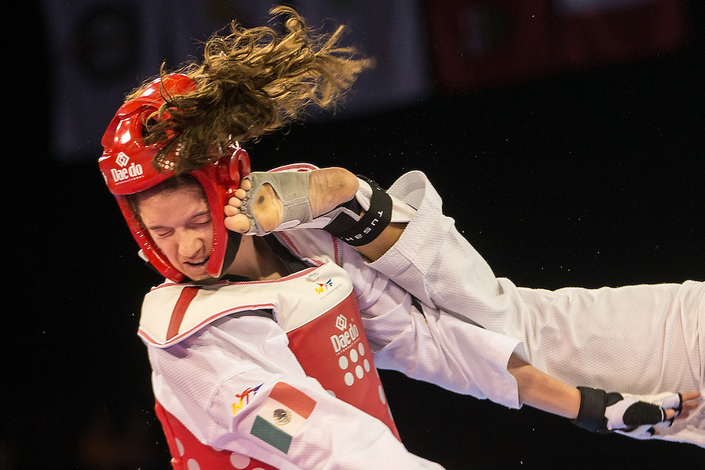 Paulina Armeria of Mexico takes a kick to the head from Cheyenne Lewis of the United States during their gold medal contest in the women's Taekwondo -57kg division of at the 2015 Pan American Games in Toronto, Canada, July 20,  2015.  AFP PHOTO/GEOFF ROBINS
