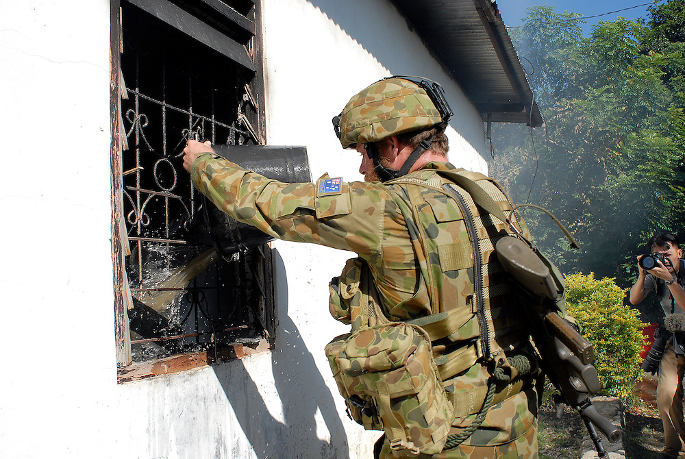 An Australian soldier helps to put out a fire lit by rival gangs. Australian peacekeepers are assigned to protect East Timorese firefighters, the Bombeiros, as they attempt to put out a major fire lit by fueding gangs. Acts of arson across Dili have become a continual occurence. Dili East Timor 060606