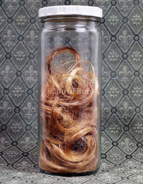 A glass bottle with blond hair.