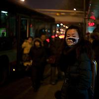 BEIJING, 15.1.2013 : Eine junge Frau mit Mundschutz gegen den derzeitigen Pekinger Smog am fruehen Abend.