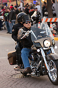 An elderly biker wearing a top hat cruises down Main Street during the 74th Annual Daytona Bike Week March 8, 2015 in Daytona Beach, Florida. More than 500,000 bikers and spectators gather for the week long event, the largest motorcycle rally in America.