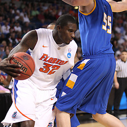 Mar 17, 2011; Tampa, FL, USA; Florida Gators center Vernon Macklin (32) drives past UC Santa Barbara Gauchos center Greg Somogyi (55) during first half of the second round of the 2011 NCAA men's basketball tournament at the St. Pete Times Forum.  Mandatory Credit: Derick E. Hingle