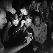 """American Steve Christiansen (L) shows a video on his Ipod to a group of men in the """"bomb village"""" of Ban Senphen. The village is located in the Ban Phanhop valley, one of the """"chokes"""", or narrow corridors along the Ho Chi Minh Trail in Laos that were heavily bombed by American forces during the Vietnam War. Much of the village infrastructure, from housing supports to boats, are constructed from the metal from downed airplanes and unexploded bombs."""