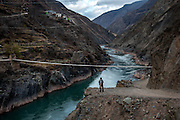 A Tibetan stands above the Lancang (Mekong) river near Deqen, Yunan, China. Fast flowing and oxydized to its blue-tint from the copper rich mountains, the river originates far to the north on the Tibetan plateau.