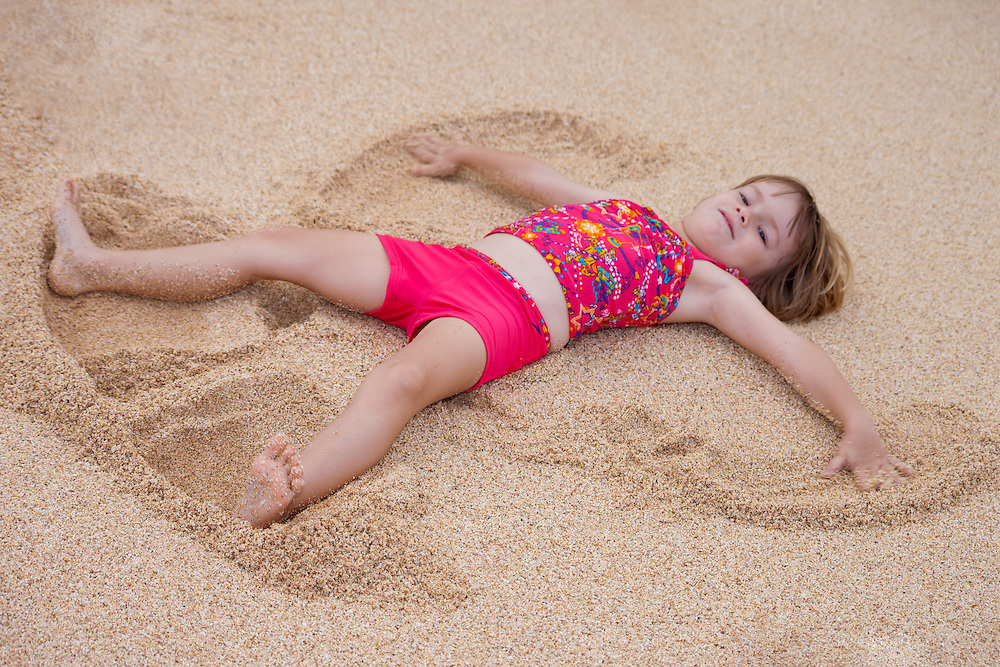 A little girl makes an 'angel' in the sand on the beach in Hawaii