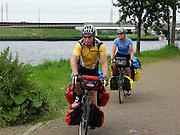 Twee Amerikaanse toeristen fietsen met volle bepakking en lange afstandsroute.<br /> <br /> Two American tourists are cycling nearby Breukelen during a holiday.