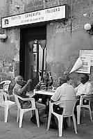 San Vito dei Normanni, centro storico. Anziani discutono bevendo una birra seduti davanti all'ingresso della vecchia sede del partito comunista italiano