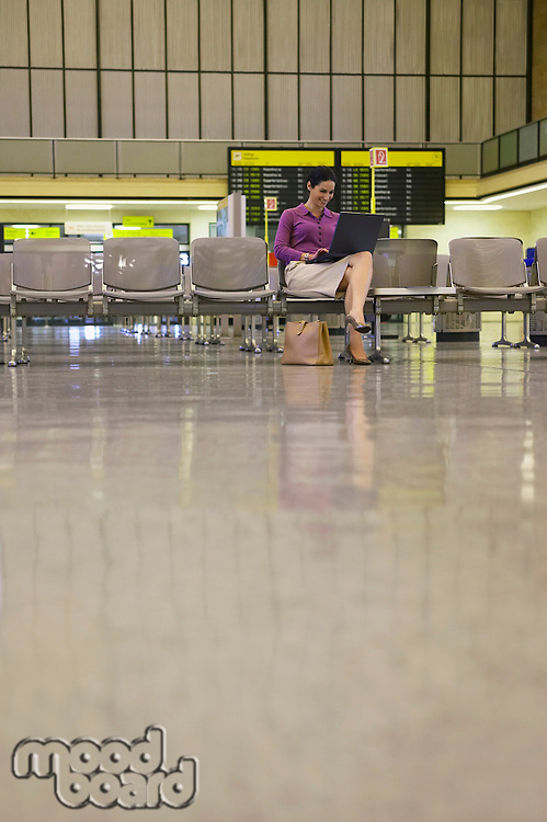 Business woman using laptop in airport lobby