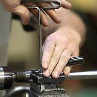 Butler tightens down the rifle barrel onto the lathe as he prepares to take of the 68,000th of an inch of metal.