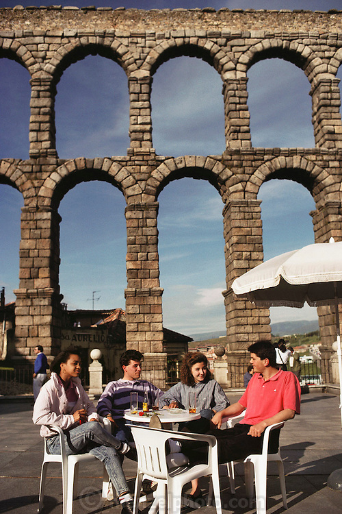 Young people at a café table under the Roman aqueduct, Segovia, Spain.