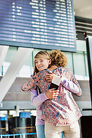 Portrait of young teenage girl reunting with her mother in airport