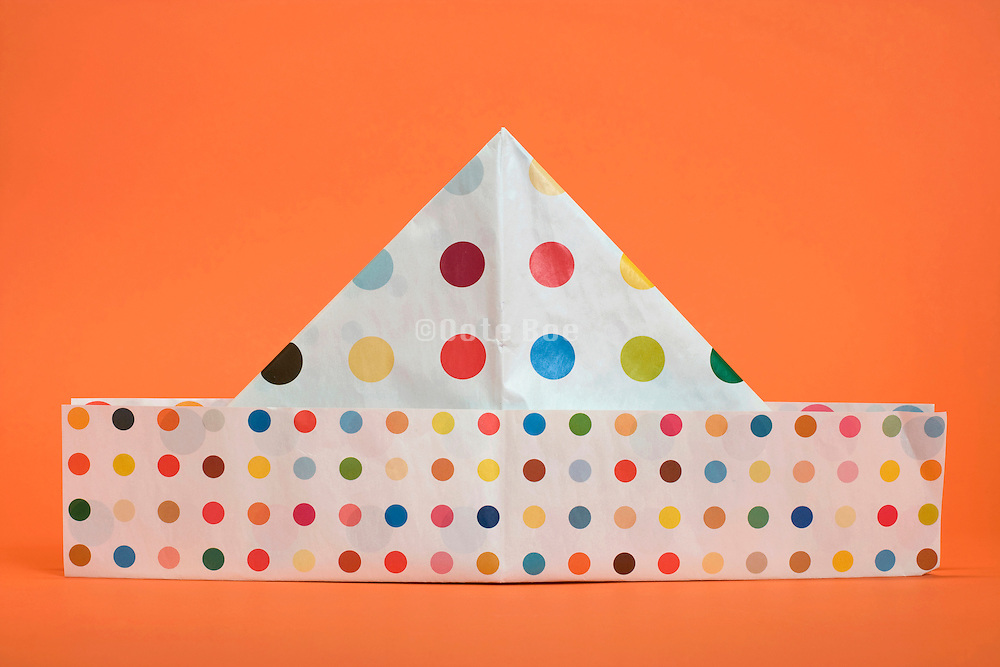 a homemade paper party hat made from Damien Hirst spot poster against an orange background