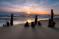 The sunset casts long shadows on old dock pilings along the Lake Michigan shore