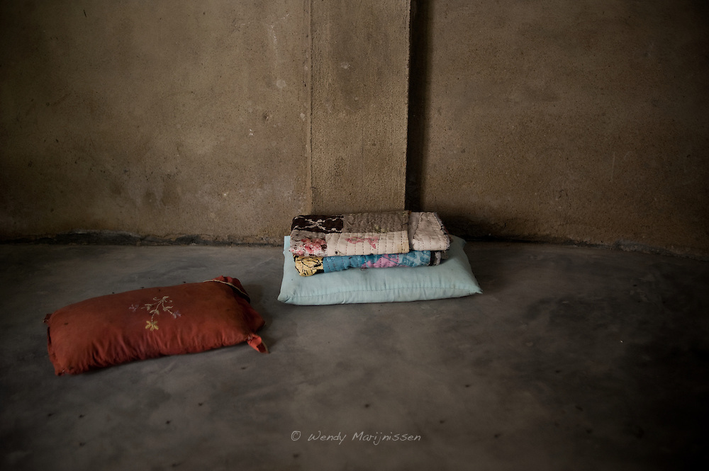 A blanket on a concrete floor is where Sherbano conducts her home deliveries. Rehri Goth, Karachi, Pakistan, 2011