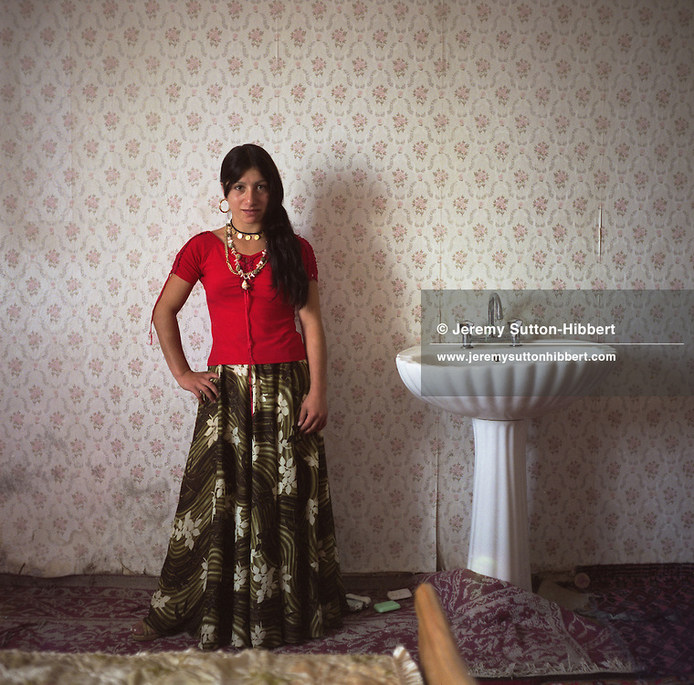 A Roma girl stands beside the wash basin in her bedroom, in a newly built home in the new part of Sintesti roma camp. Many of the furnishings in the new houses are bought as status symbols, a sign of their new wealth.