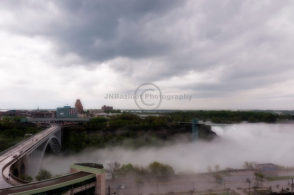 Fog rolls along the Niagara River and under Rainbow Bridge in Niagara Falls, Canada/US.