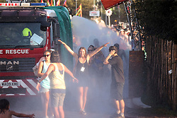 © London news Pictures. 21/06/2017. Glastonbury, UK. Revellers cool down in water from a fire engine while enjoying day one of the 2017 Glastonbury Festival. The five-day festival of contemporary performing arts is the highlight of the British festival season. Photo credit: Jason Bryant/LNP